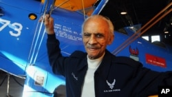 FILE - Former Tuskegee Airman Herbert Carter, 94, of Tuskegee, Alabama, poses with a PT-17 trainer aircraft in a hangar at Tuskegee Airmen National Historic Site at Moton Field in Tuskegee, Jan. 18, 2012.
