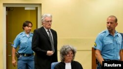 FILE - Bosnian Serb wartime leader Radovan Karadzic appears in the courtroom for his appeals judgement at the International Criminal Tribunal for Former Yugoslavia at The Hague.
