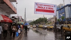 In this photo taken on Monday, July 28, 2014, people hang out in a street under a banner with caution about Ebola, in Monrovia, Liberia.