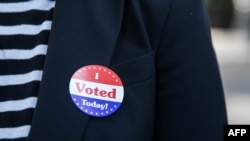 "Lisa O. wears an ""I Voted Today!"" sticker after casting her vote during early voting at City Hall in Philadelphia, Pennsylvania on October 7, 2020. (Photo by GABRIELLA AUDI / AFP)"