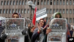 FILE - Women hold copies of Zaman newspaper, headlined 'Black Day of Democracy,' to protest the detention of its editor and other journalists in raids by the Turkish government in Ankara.
