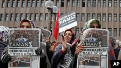 """Women hold copies of Zaman newspaper with a headline that reads """"the black day of democracy """" as they protest against the detention of its editor-in-chief a day ago in Istanbul, outside the Palace of Justice in Ankara, Turkey, Dec. 15, 2014."""