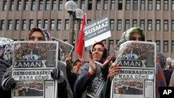 """Phụ nữ cầm báo Zaman với tin hàng đầu """"Ngày đen tối của Dân chủ"""" trong khi tham gia biểu tình trong thủ đô Ankara của Thổ Nhĩ Kỳ, phản đối việc câu lưu tổng biên tập nhật báo này, 15/12/14"""