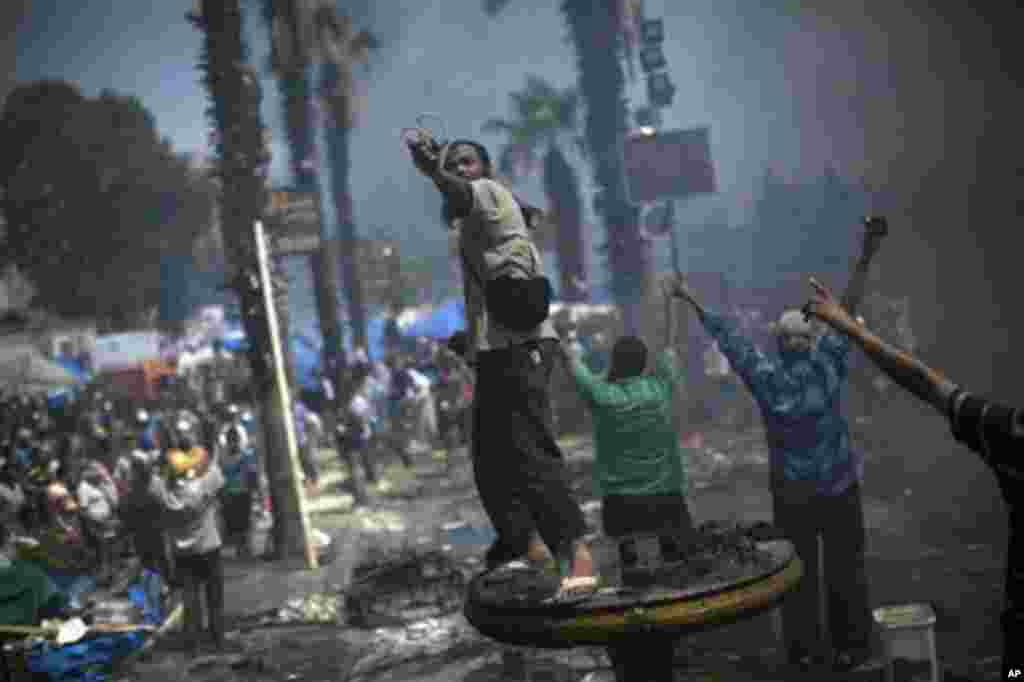 A supporter of ousted Islamist President Mohammed Morsi shoots a slingshot against Egyptian security forces.