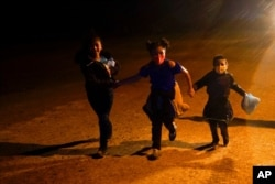 FILE - Three young migrants hold hands as they run in the rain at an intake area after turning themselves in upon crossing the U.S.-Mexico border, May 11, 2021, in Roma, Texas.