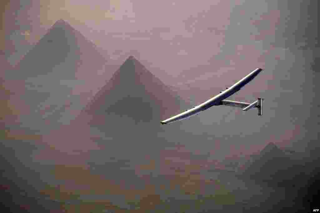 This handout photo released by Solar Impulse 2 shows the solar powered plane, piloted by Swiss pioneer André Borschberg, during the flyover of the pyramids of Giza prior to landing in Cairo, Egypt.