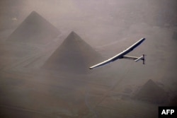 This handout photo released by Solar Impulse 2 shows the solar powered plane, piloted by Swiss pioneer André Borschberg, during the flyover of the pyramids of Giza on July 13, 2016 prior to landing in Cairo, Egypt.