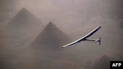 FILE - This handout photo released by Solar Impulse 2 shows the solar-powered plane, piloted by André Borschberg, during the flyover of the pyramids of Giza prior to landing in Cairo, July 13, 2016.
