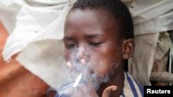 FILE - Abdulahi Yaroow, 13, smokes a cigarette while chewing khat at the same time in Mogadishu, Somalia, Aug. 10, 2014.