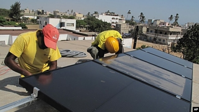 Prosolia technicians Mamadou Ba, left, and Mouhamed Diedhiou install solar panels on a vocational school in Dakar, Senegal, Dec. 1, 2011.