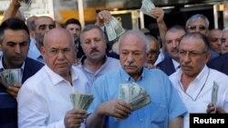 ترک تاجر ڈالر لیے زر مبادلہ کا لین دین کرنے والے ایک دفتر کے سامنے کھڑے ہیں۔ صدر اردوان نے قوم سے اپیل کی تھی کہ وہ ترک کرنسی لیرا کو سہارا دینے کے لیے اسے اپنے ڈالروں سے تبدیل کر لیں۔ 14 اگست 2018