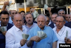 Businessmen holding U.S. dollars stand in front    of a currency exchange office in response to the call of Turkish President Tayyip Erdogan on Turks to sell their dollar and euro savings to support the lira, in Ankara, Turkey Aug. 14, 2018.