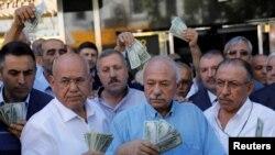 Doanh nhân cầm đô la Mỹ đứng trước một văn phòng đổi tiền, đáp lời kêu gọi của Tổng thống Thổ Nhĩ Kỳ Tayyip Erdogan kêu gọi người dân bán tiền đô và tiền euro để dành để ủng hộ đồng lira của Ankara.