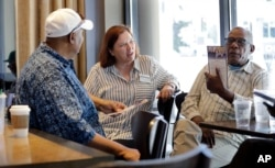 In this photo taken Monday, June 10, 2019, Seattle City Council candidate Pat Murakami, center, talks with voters in a coffee shop about her campaign in Seattle. (AP Photo/Elaine Thompson)