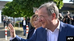 Armin Laschet, leader of Germany's conservative Christian Democratic Union (CDU) party and candidate for Chancellor, and his wife Susanne Laschet (L) leave after voting at a polling station in Aachen, western Germany, Sept. 26, 2021