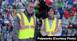 Paul Tasner and Elena Olivari talk to investors standing in front of a mountain of plastic trash.