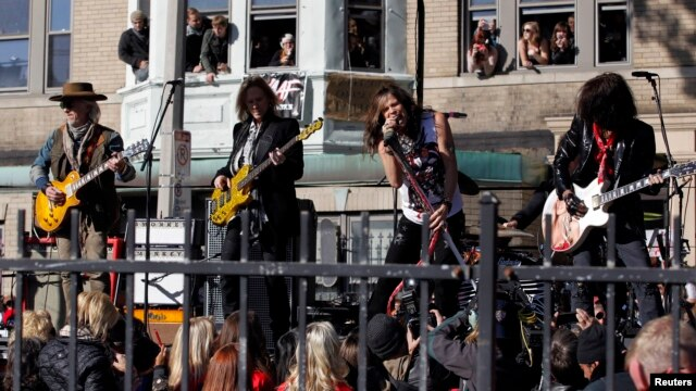 Members of the band Aerosmith (L-R) Brad Whitford, Tom Hamilton, Steven Tyler and Joe Perry perform in front of their old apartment building in Allston, Massachusetts, Nov. 5, 2012.