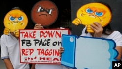"""FILE - People covering their faces with """"angry emoji"""" cutouts protest Facebook's alleged inaction against fake news, hate speech and red-tagging of activists, in suburban Taguig city, east of Manila, Philippines, May 9, 2019."""