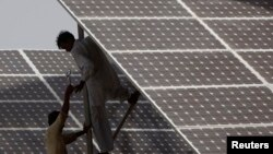 FILE - Technicians work on a solar panel about 25 km (15 miles) from Karachi, Pakistan, June 18, 2010.