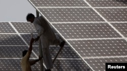 FILE - Technicians work on solar panel in power station at Hub about 25 km (15 miles) from Karachi, Pakistan.