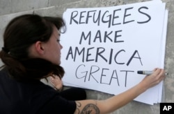 Protester Emily Nostro prepares a sign for a rally against President Donald Trump's executive order on Muslim immigration in downtown Miami, Jan. 22, 2017.