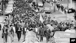 FILE - In this March 17, 1965, file photo, demonstrators walk to the courthouse behind the Rev. Martin Luther King Jr. in Montgomery, Alabama. (AP Photo/File)
