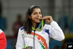 India's Sakshi Malik poses with her bronze medal for the women's wrestling freestyle 58-kg competition during the medals ceremony at the 2016 Summer Olympics in Rio de Janeiro, Brazil, Wednesday, Aug. 17, 2016.