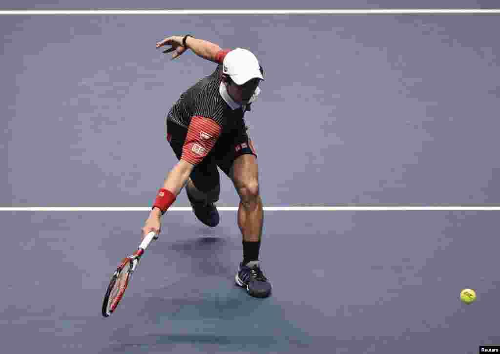 Tay vợt Kei Nishikori của Nhật Bản đánh bóng cho tay vợt David Ferrer của Tây Ban Nha trong trận chung kết ATP World Tour Bảng B tại Sân O2 ở London.