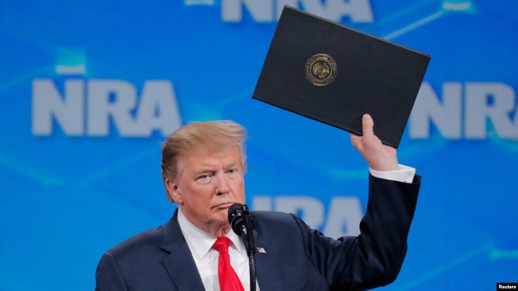 Tổng thống Donald Trump giơ cao một sắc lệnh khi loan báo Mỹ sẽ rút ra khỏi Hiệp ước Buôn bán Võ khí.