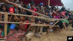 FILE - Rohingya Muslim children, who crossed over from Myanmar into Bangladesh, are squashed together as they wait to receive food handouts distributed to children and women by a Turkish aid agency at Thaingkhali refugee camp, Bangladesh, Oct. 21, 2017.