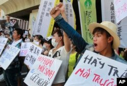FILE - Vietnamese activists shout slogans and hold placards during a protest to urge Taiwan-owned steel plant Formosa Ha Tinh to take responsibilitiy for the clean-up of its toxic wastewater spill that killed thousands of fish in Vietnam, in Taipei, Taiwan, Aug. 10, 2016. The April 2016 Ha Tinh fish kill and its public exposure by bloggers and social media is widely seen as having raised environmental awareness and activism among Vietnamese.