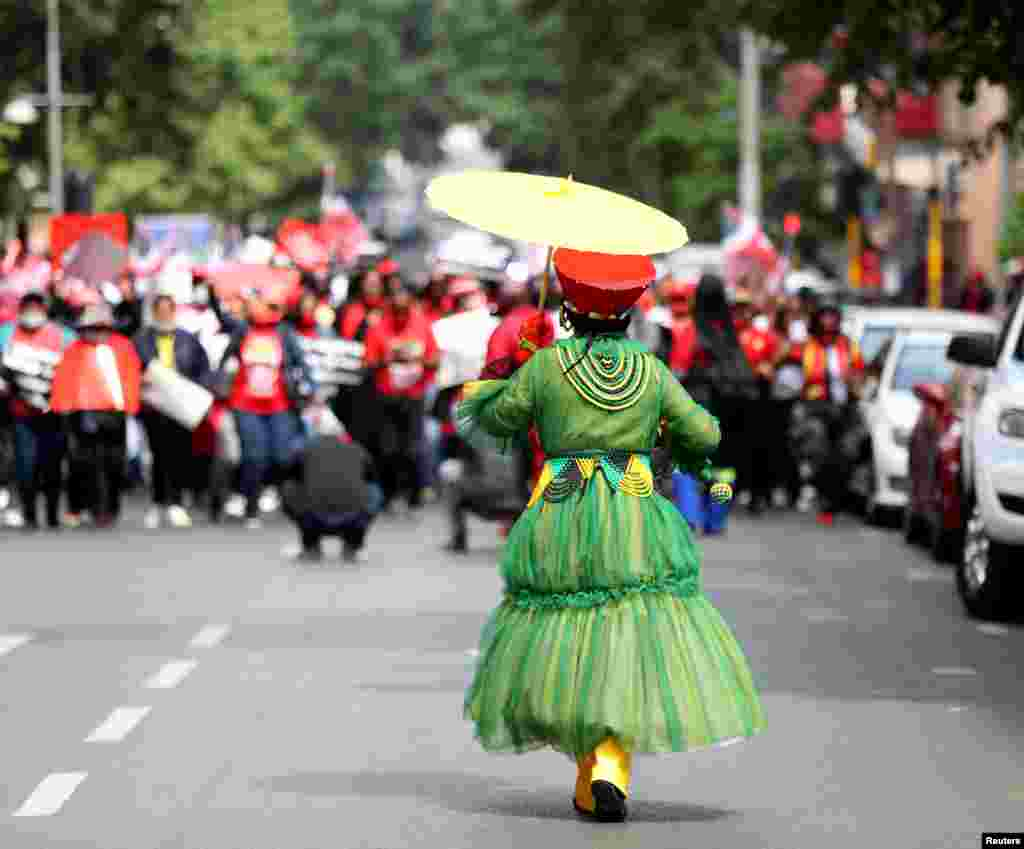 A member of the Congress of South African Trade Unions (COSATU) joins others taking part in a nationwide strike over issues including corruption and job losses, outside parliament in Johannesburg.