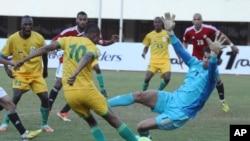 Le joueur zimbabwéen Obvious Karuru, à gauche, décoche un tir que le gardien égyptien Ahmed Ekram tente de repousser lors d'un match de qualification de Coupe du Monde entre le Zimbabwe et l'Egypte au Stade national des sports à Harare, dimanche 9 juin 2013.