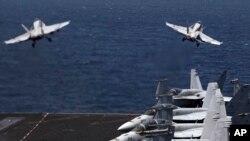 Jet tempur F/A-18 lepas landas untuk misi di Irak dari kapal USS George H.W. Bush di Teluk Persia.
