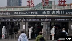 北京地铁站保安人员身穿防护服检测地铁乘客的体温。(2020年1月27日)