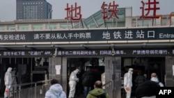 北京地鐵站保安人員身穿防護服檢測地鐵乘客的體溫。 (2020年1月27日)