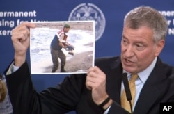 FILE - New York City Mayor Bill de Blasio displays a photo on Nov. 18, 2015, of a Syrian boy who drowned when his family tried to flee the war.