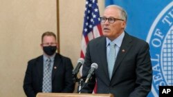 Washington Gov. Jay Inslee, right, speaks at a news conference, Aug. 18, 2021, at the Capitol in Olympia.