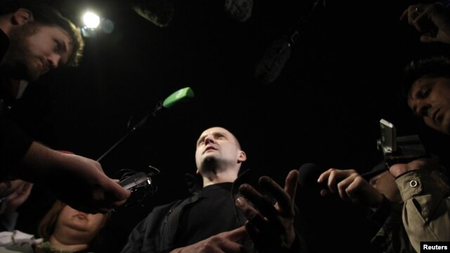 Opposition leader Sergei Udaltsov (C) talks to the media after leaving a building of the Russian Investigative Committee in Moscow, October 17, 2012. Russian investigators have begun criminal proceedings against the prominent leader of protests against Pr