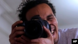 Mahmoud Abu Zaid, a photojournalist known as Shawkan, poses with his colleague's camera at his home in Cairo, Egypt, March 4, 2019. Shawkan was released after five years in prison.
