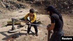 28일 시리아 반군이 점령하고 있는 데라 지역 주민들이 고장난 물 펌프를 고치고 있다.