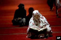 Seorang perempuan tengah membaca Al Qur'an di dalam masjid Istiqlal, Jakarta. (Foto: dok).