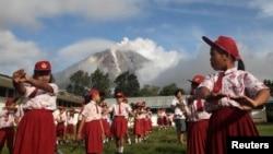 Murid-murid sekolah di desa Berastepu, Karo, melakukan senam pagi dengan latar belakang Gunung Sinabung yang mengeluarkan abu (7/11). (Reuters/Tarmizy Harva)