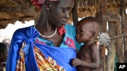 FILE - Elizabeth Nyakoda holds her severely malnourished 10-month-old daughter at the feeding center for children in Jiech, Ayod County, South Sudan, Dec. 10, 2017.