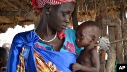 FILE - Elizabeth Nyakoda holds her severely malnourished 10-month old daughter at the feeding center for children in Jiech, Ayod County, South Sudan, Dec. 10, 2017.