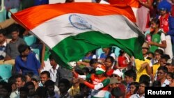FILE - A fan waves an Indian flag during a cricket match against England, Nov. 19 ,2016. Amazon pulled doormats depicting the Indian flag.
