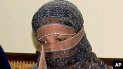 FILE - Pakistani Christian woman Asia Bibi, listens to Governor of Pakistani Punjab Province Salman Taseer, unseen, at a prison in Sheikhupura near Lahore, Nov. 20, 2010.