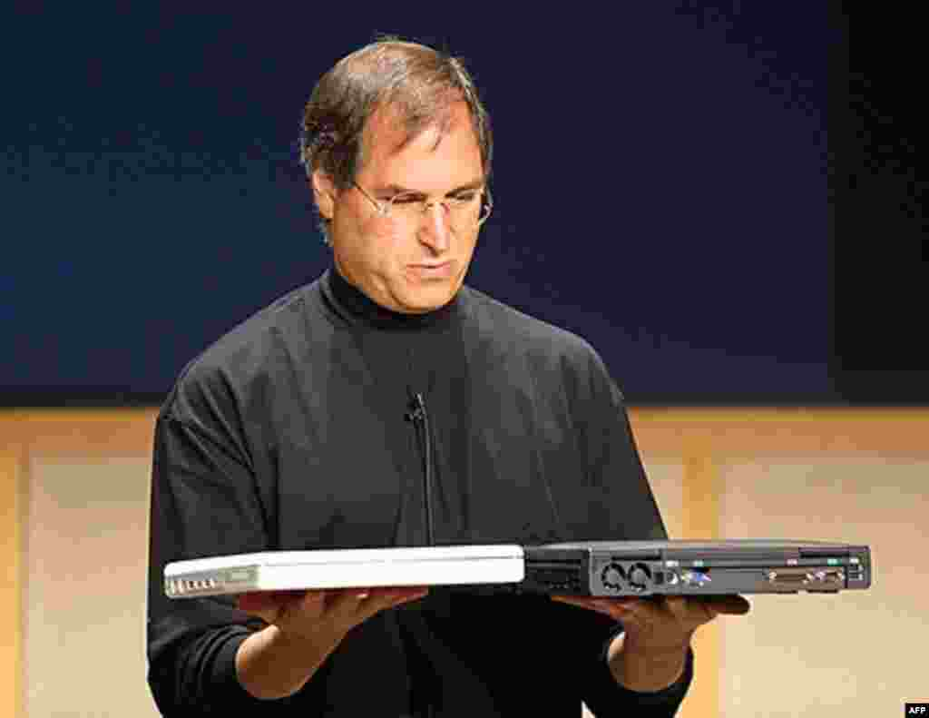 Steve Jobs compares the weight of the all new iBook notebook computer weighing just 4.9 pounds (L) and a Dell computer notebook during a Apple Media event in Cupertino, California 01 May 2001. (AFP)