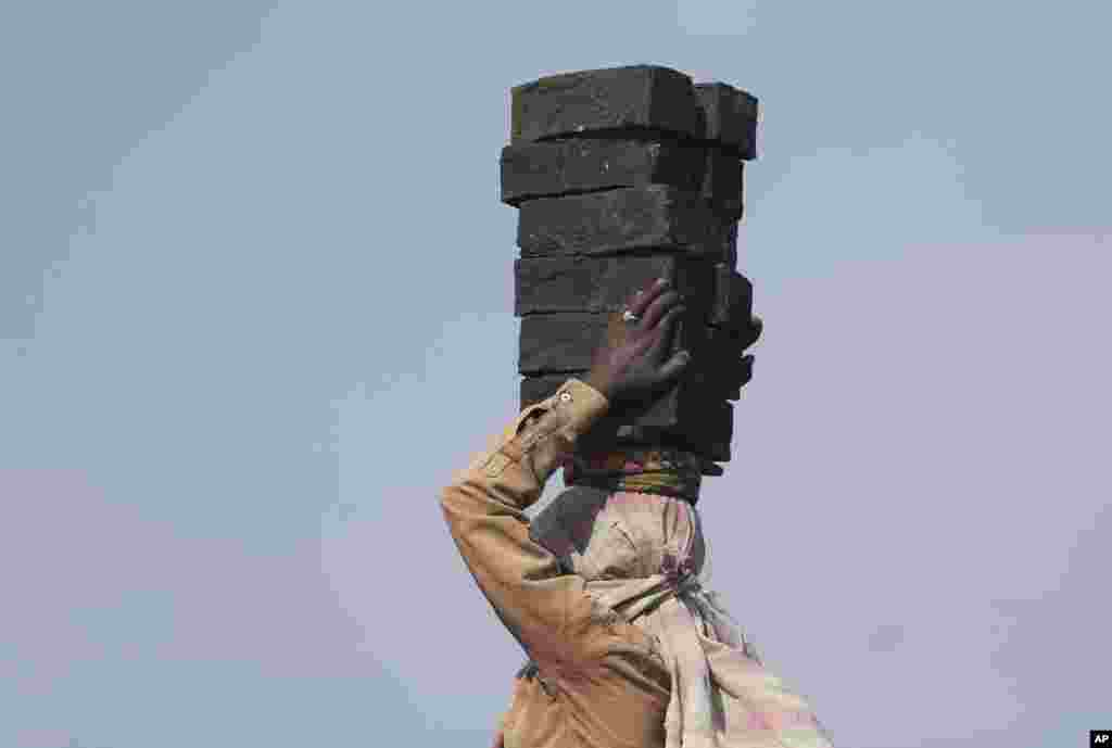 A woman carries bricks at a brick kiln on the outskirts of Hyderabad, India.