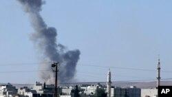 7일 터키 쪽에서 바라본 시리아 접경도시 코바니에서 공습으로 인한 검은 연기가 솟아오르고 있다. 이스람 수니파 무장단체 ISIL은 시리아 북부 쿠루드 마을 수백 곳을 점령한데 이어, 코바니 일부도 장악했다.